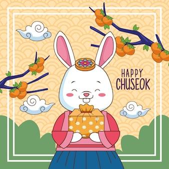 Szczęśliwy chuseok celebracja z królikiem podnoszącym prezent i gałęziami drzew