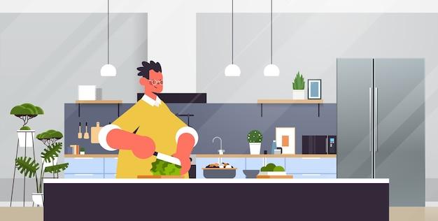 Szczęśliwy człowiek cięcia sałaty przygotowanie sałatki ze świeżych warzyw zdrowe odżywianie gotowanie w domu koncepcja nowoczesnej kuchni wnętrza poziomy portret