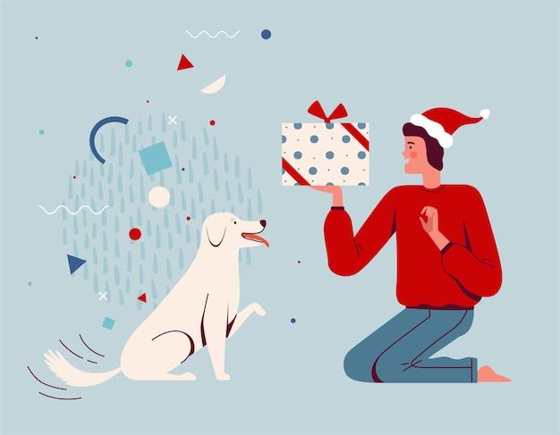 Szczęśliwy człowiek w santa hat daje prezent na boże narodzenie swojemu psu. wychowywanie i szkolenie szczeniaka. impreza dla zwierząt. kreskówka mieszkanie.