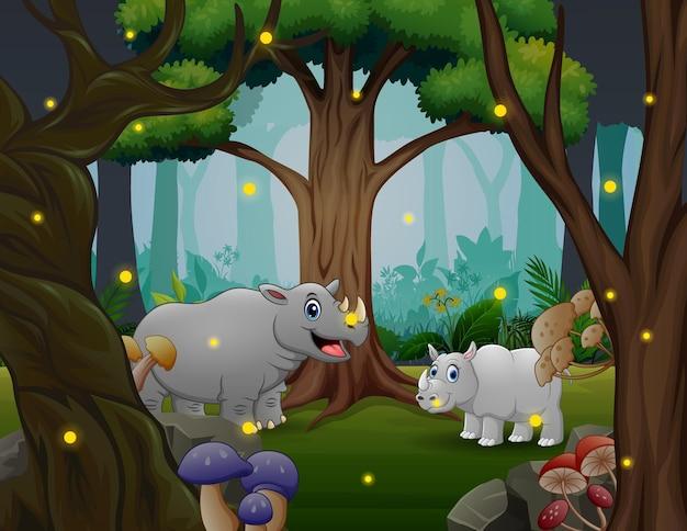Szczęśliwy duży nosorożec ze swoim młodym bawiącym się w dżungli