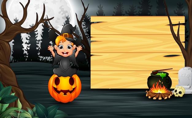 Szczęśliwy dzieciak jest ubranym czarownica kostiumowego stojaka obok drewnianej deski