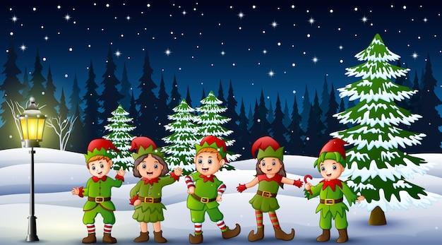 Szczęśliwy dzieciak jest ubranym elfa kostium w snowing wzgórzu