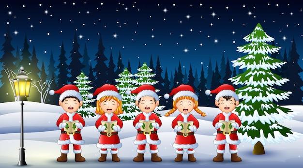 Szczęśliwy dzieciak jest ubranym santa kostiumowego śpiew w snowing ogródzie