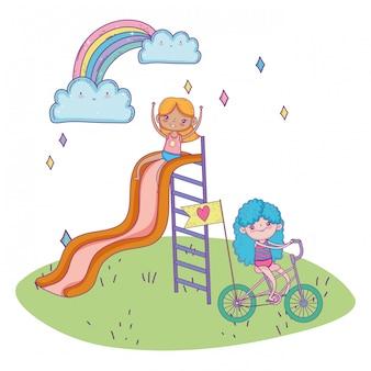 Szczęśliwy dzień dziecka, dziewczynka bawi się w zjeżdżalni i jazda rowerem w parku