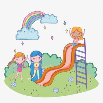 Szczęśliwy dzień dziecka, słodkie dziewczyny bawiące się w parku zjeżdżalni