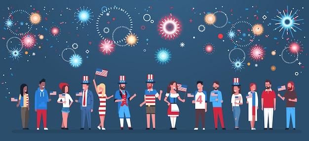 Szczęśliwy dzień niepodległości 4 lipca łączą tradycyjne rasy ludzi z tradycyjnymi ubraniami z amerykańskimi flagami świętującymi czapki nad fajerwerkami