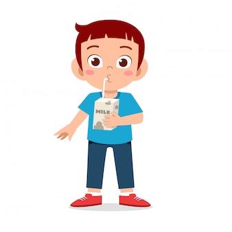 Szczęśliwy ładny chłopak pić świeże mleko