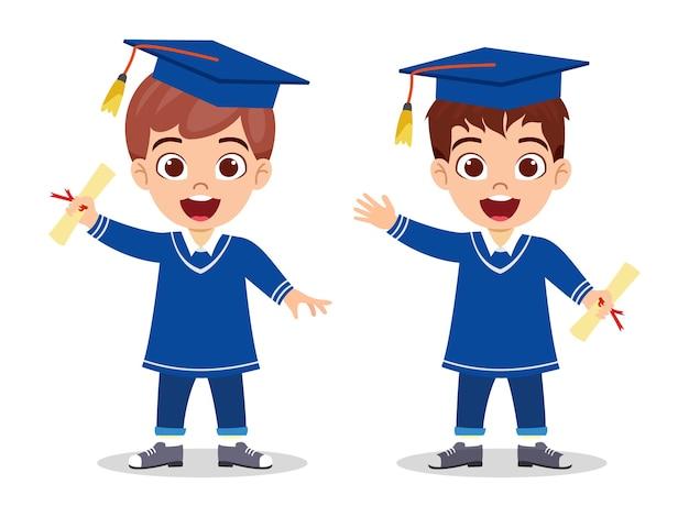 Szczęśliwy ładny dzieciak absolwent chłopców stojący z certyfikatem i macha na białym tle