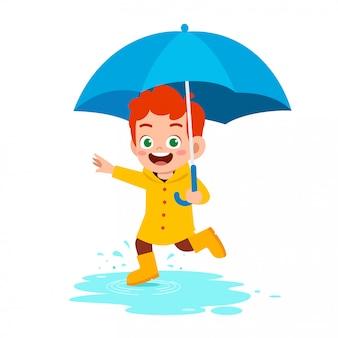 Szczęśliwy ładny dzieciak chłopiec grać nosić płaszcz przeciwdeszczowy