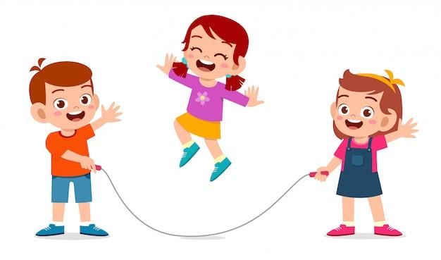 Szczęśliwy ładny dzieciak chłopiec i dziewczynka grać skakanka