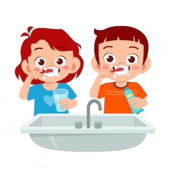 Szczęśliwy ładny dzieciak chłopiec i dziewczynka szczotkować czyste zęby