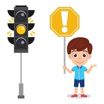 Szczęśliwy ładny dzieciak chłopiec z znak drogowy trzymając znak ostrzegawczy na białym tle