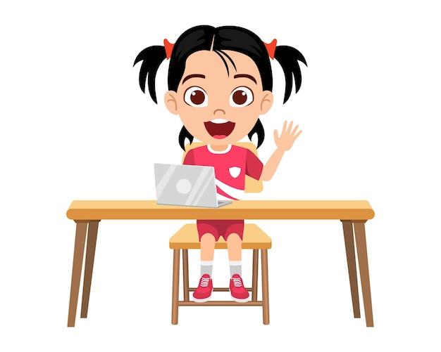Szczęśliwy ładny inteligentny dzieciak dziewczyna robi zajęcia e-learningowe na biurku z laptopem z wesołym wyrazem na białym tle nauka w domu kursy internetowe lub samouczki