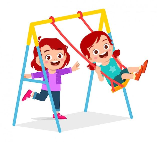 Szczęśliwy ładny małe dziecko chłopiec i dziewczynka grać huśtawka
