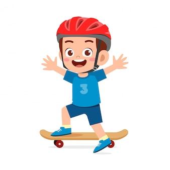 Szczęśliwy ładny mały chłopiec dziecko grać na deskorolce