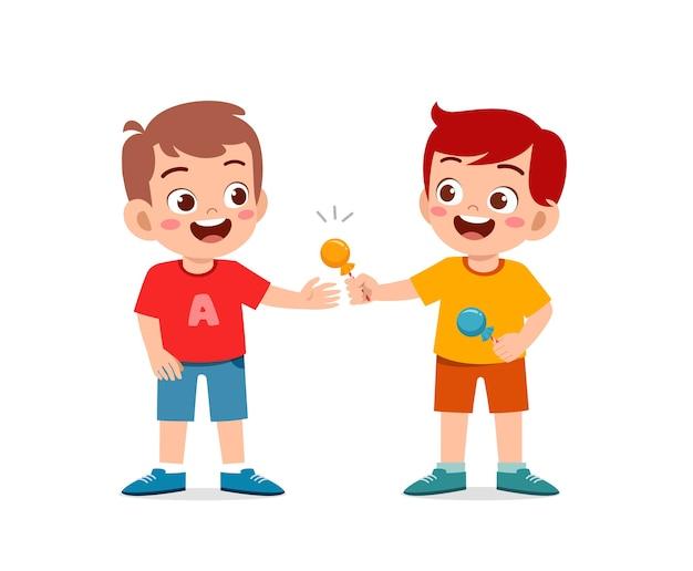 Szczęśliwy ładny mały chłopiec i dziewczynka dzielą się jedzeniem z przyjacielem