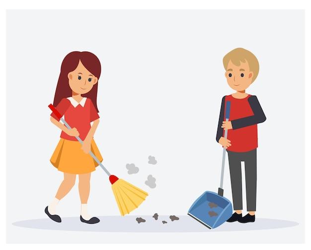 Szczęśliwy ładny mały chłopiec i dziewczynka pomagając sobie nawzajem do czyszczenia. dziewczyna zamiata podłogę, a chłopiec trzyma szufelkę na śmieci.