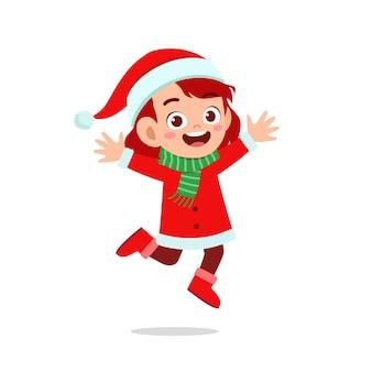 Szczęśliwy ładny mały chłopiec i dziewczynka ubrana w czerwony świąteczny kostium i skok
