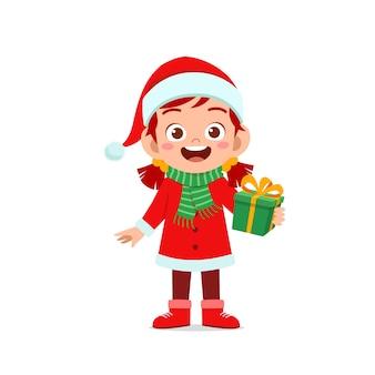Szczęśliwy ładny mały chłopiec i dziewczynka ubrana w czerwony świąteczny kostium i trzymając prezent
