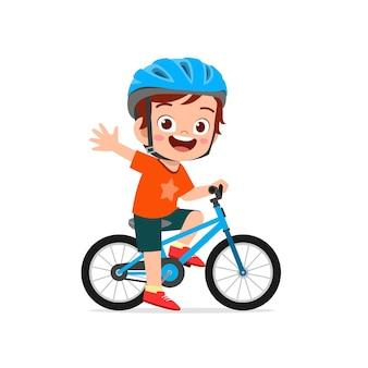 Szczęśliwy ładny mały chłopiec jedzie na rowerze