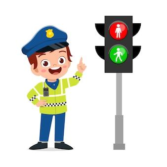 Szczęśliwy ładny mały chłopiec na sobie mundur policyjny i stanąć obok lampy drogowej