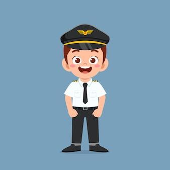 Szczęśliwy ładny mały chłopiec nosi mundur pilota