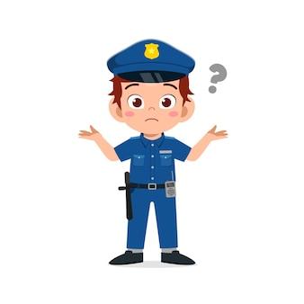 Szczęśliwy ładny mały chłopiec nosi mundur policyjny i myśli znakiem zapytania