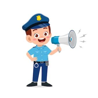Szczęśliwy ładny mały chłopiec nosi mundur policyjny i trzyma megafon