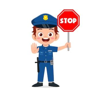 Szczęśliwy ładny mały chłopiec nosi mundur policyjny i trzyma znak stopu