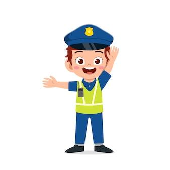 Szczęśliwy ładny mały chłopiec nosi mundur policyjny i zarządza ruchem