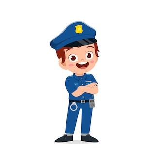 Szczęśliwy ładny mały chłopiec nosi mundur policyjny