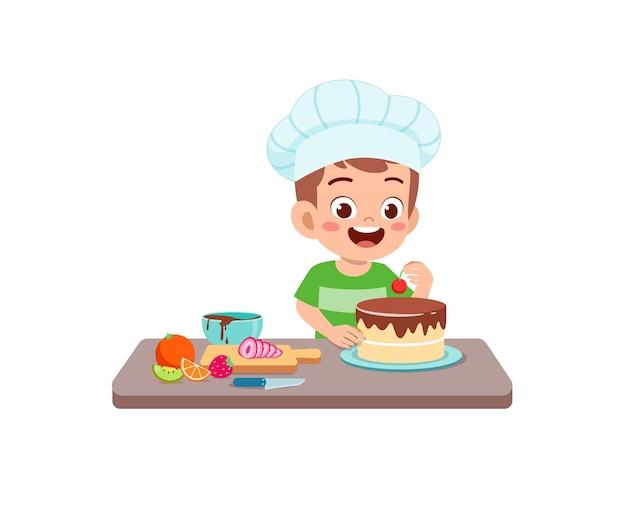 Szczęśliwy ładny mały chłopiec nosić mundur szefa kuchni i gotować tort urodzinowy