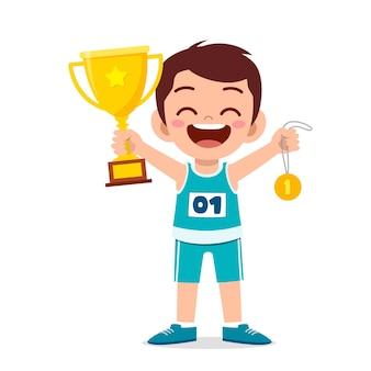 Szczęśliwy ładny mały chłopiec trzyma złoty medal i trofeum
