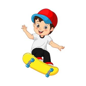 Szczęśliwy mały chłopiec grający na deskorolce