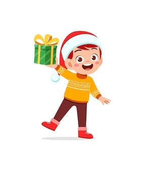 Szczęśliwy mały chłopiec trzyma prezent na boże narodzenie