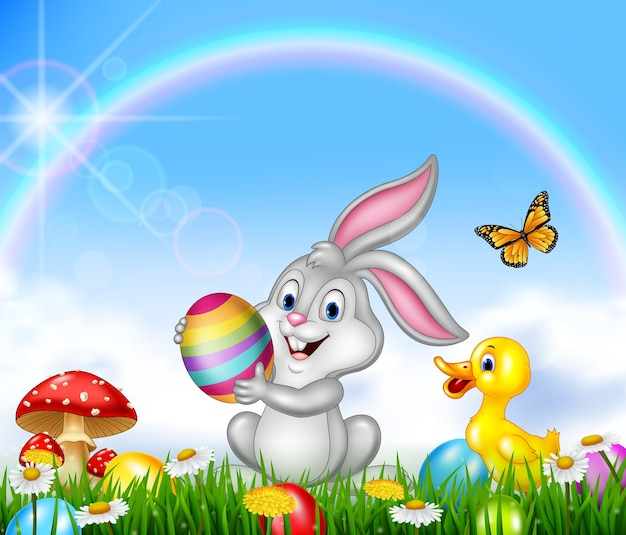 Szczęśliwy mały królik trzyma wielkanocnego jajko