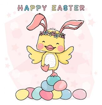 Szczęśliwy mały żółty kurczak z uszami królika, stojący na stosie kolorowych pastelowych pisanek