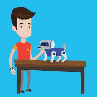 Szczęśliwy młody człowiek bawić się z mechanicznym psem.
