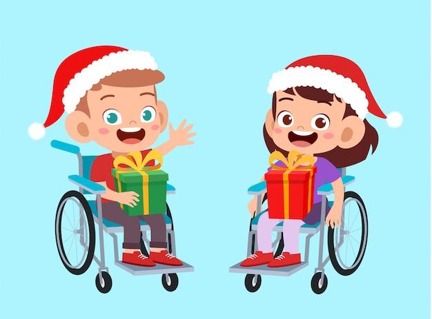 Szczęśliwy przyjaciel niepełnosprawny daje prezent dzieciom w boże narodzenie