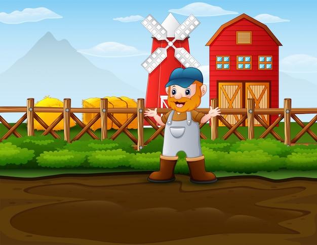 Szczęśliwy rolnik mężczyzna stoi przed jego stodoła