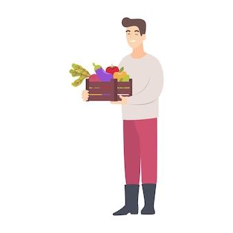 Szczęśliwy rolnik ze świeżo zebranymi warzywami i owocami w pudełku. ogrodnik trzyma pudełko ze zbiorami