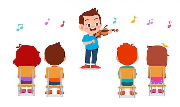 Szczęśliwy śliczny chłopiec bawić się skrzypce w klasie