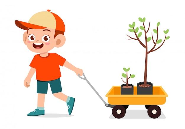 Szczęśliwy śliczny dzieciak chłopiec ciągnienia furgon z drzewem