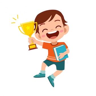 Szczęśliwy śliczny dzieciak chłopiec wygrywa gemowego złotego trofeum