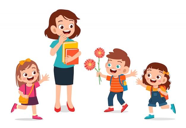 Szczęśliwy śliczny dzieciak daje kwiatu nauczyciel