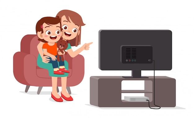 Szczęśliwy śliczny dzieciak ogląda tv z rodziną wpólnie
