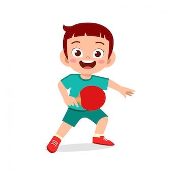 Szczęśliwy słodki chłopiec gra w ping ponga