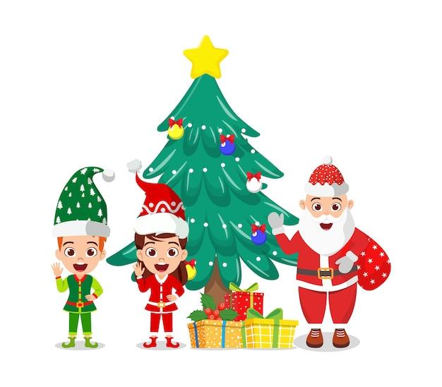 Szczęśliwy słodki chłopiec i dziewczynka oraz święty mikołaj machający i świętujący wesołe charyzmaty z pudełkami na prezenty i drzewem charyzmatów na białym tle