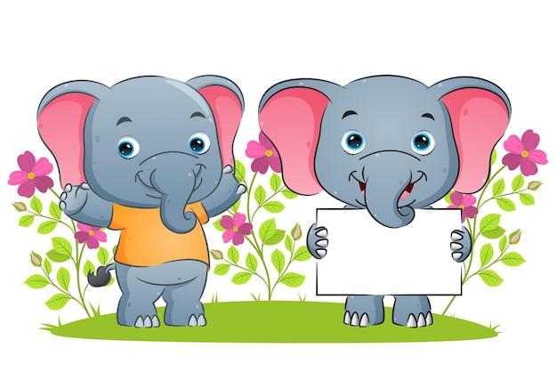 Szczęśliwy słoń trzyma pustą tablicę i podaje ilustrację wspierającą