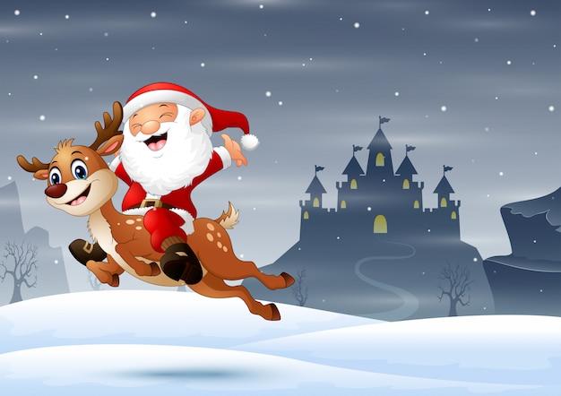 Szczęśliwy święty mikołaj jedzie reniferowego doskakiwanie na śniegu